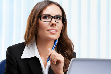 Thinking businesswoman working with laptop