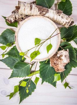 Xylitol - sugar substitute. Birch sugar on white wooden background.