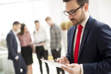 Hardworking businessman dressed in suit standing in modern office and using tablet