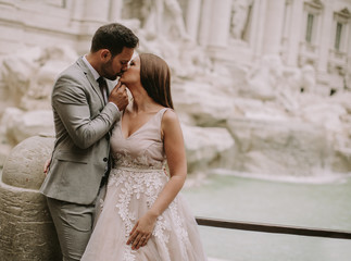Bride and groom posing in front of Trevi Fountain (Fontana di Trevi), Rome, Italy