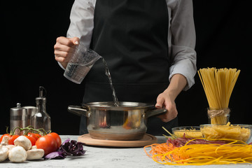 The chef pours water into the pan, on a black background, with pasta on the table, vegetables and spaghetti, mushrooms. The concept of cooking spaghetti, pasta, soup, and food