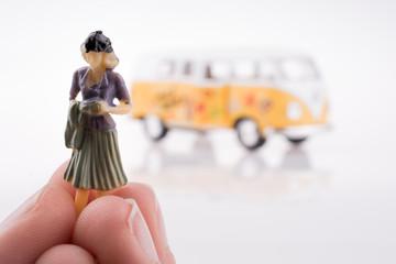 Hand holding a figure near a van
