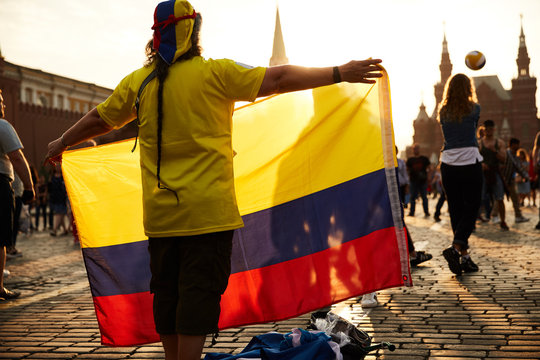 A football fan from colombia standing on the red square in moscow during the world cup posing to a photographer