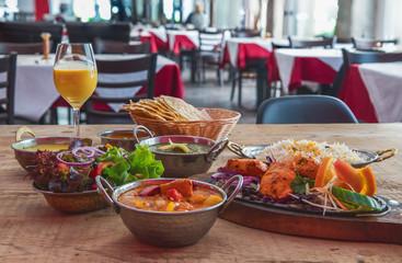 Indisches Essen mit Nan, Masal, Salat, Chicken Tandoori,  Tikka, Spinat, Basmati schön angerichtet in einem Restaurant auf einem Holztisch serviert