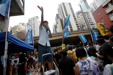 Pro-democracy activist Joshua Wong wave to supporters during a protest march in Hong Kong