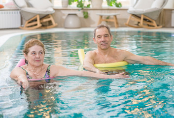 aged people doing aqua fitness with swim noodles