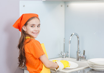 Smiling little girl in an apron washes the dishes at the sink