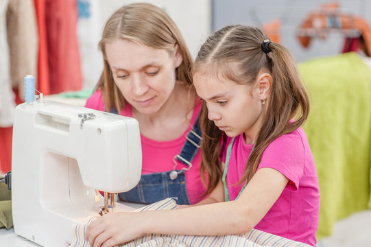 mother and little girl together sews on sewing machine