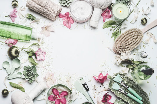 Spa and wellness background with  flowers, skin cosmetic products and others body care and massage accessories on white background, top view, frame with copy space