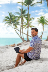 Successful freelancer businessman with laptop on the beach