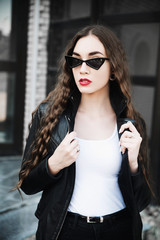 Young woman wearing leather jacket and sunglasses