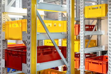 Yellow and red plastic boxes on the shelving of an industrial warehouse. Modern warehouse equipment.
