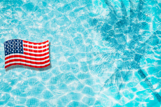 Pool float, ring floating in a refreshing blue swimming pool with palm tree leaf shadows in water