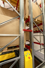 Large cardboard boxes stand on the shelves of a very high metal rack.