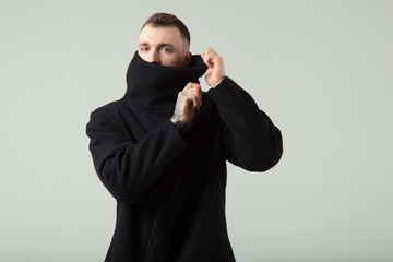 Handsome male fashion model. A man in a black stylish coat, face is covered with a collar.