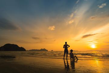 couple enjoying on the beach with beautiful sunset in Haad Chao Mai beach, Trang, Thailand.