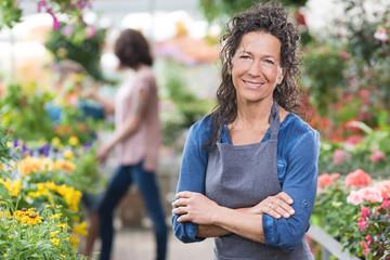 Stolze Gärtnerin steht lächelnd in Ihrem Gewächshaus
