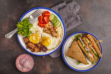 Fried eggs with bacon and a sandwich with meat, cheese and vegetables on dark background. Delicious hearty breakfast.
