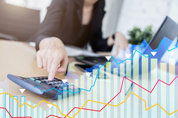 business woman working with laptop hand close up with document and paper and financial stock graph chart  diagram
