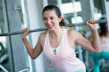 attractive woman exercise schedule time in gym workout on weight training machine