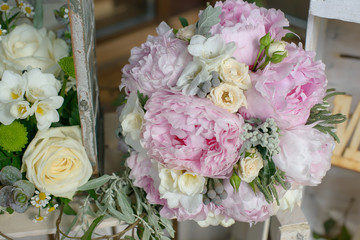 Cropped shot of pale pink hues bouquet featuring peonies, freesias and green leafy accessories, prepared for special occasions, weddings or events, or as a bouquet carried by the bride or bridesmaids