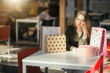 caucasian woman with shopping bags sitting at table and think or unhappy