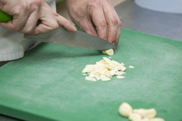 Hands of the chef cutting garlic