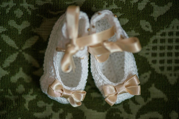 Little baby girl booties in white with beige ribbons, view from above against an ornate cushion background, adorable footwear reserved for Christening or special events