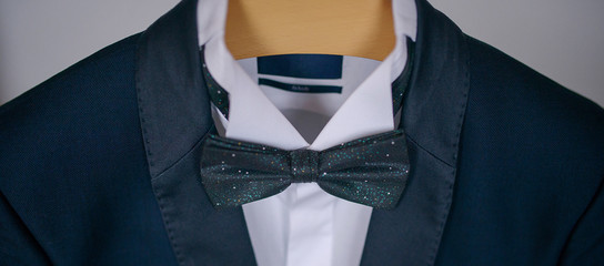 Cropped shot of elegant navy blue suit with white shirt and bow tie, male accessories for formal attire, classy groom, sophisticated businessman, or sartorial outfit for a high-paid job interview
