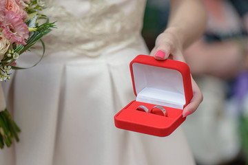 Cropped shot of Caucasian woman, holding a jewelry box with matching silver or platinum wedding rings, designated person for carrying the bands, either the bridesmaid, a family member or a close guest