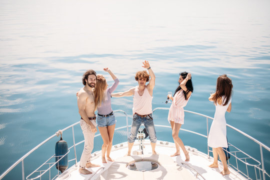 group of stylish friends on a yacht over sea background, dancing and having party on a sailing boat - Tourists on vacation