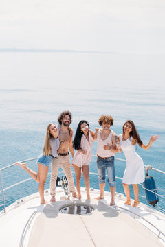 Handsome curly man and two caucasian elegant women friends drinking wine, dancing at exclusive boat party. Yachting in summer vacation. Cruise, Travel, vacation and youth lifestyle concept