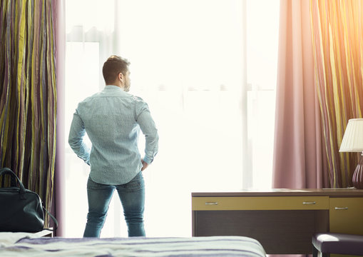 Young man looking out of the window in hotel room