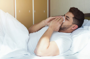 Young man sneezing and covering nose with tissue lying on bed
