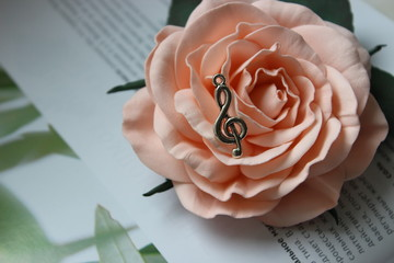 Beautiful vintage pendant in the form of a violin key on the background of a rose flower. Beautiful vintage close-up picture, concept with musical direction