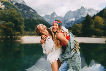 Two young tourist women have fun on the lake
