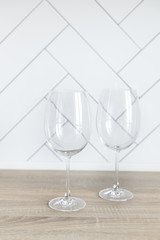 Two empty big glasses for wine on a light background