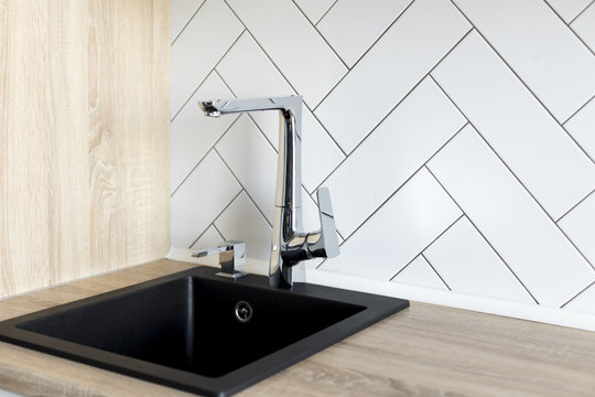 Designer kitchen with a wooden tabletop and a stainless steel faucet and a black sink
