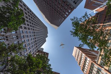 A plane flying over the modern blue cubic buildings located at The Hague city, Netherlands Wall mural
