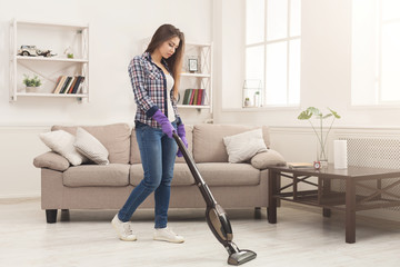 Young woman cleaning house with vacuum cleaner