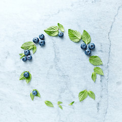 An arrangement of blueberries and mint leaves on gray marble background. Flat lay. Copy space.