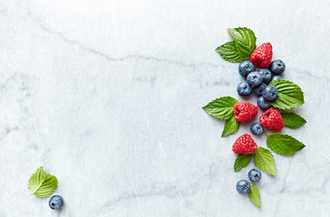 An Arrangement of fresh raspberries, blueberries  and mint leaves on gray marble background. Flat lay. Healthy diet concept.