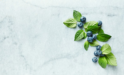 An arrangement of  blueberries with mint leaves on gray marble background. Flat lay. Copy space.