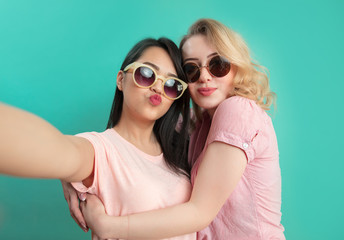 Close up portrait of two diverse young women ethnic friends in summer clothes, wearing sunglasses hugging each other while making selfie with duck lips at blue studio background