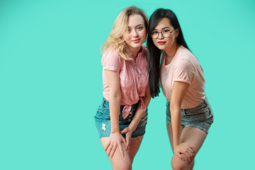 Two positive multiethnic young girlfriends standing head to head, leaning to camera, while posing at studio over blue background with copyspace. Woman Apparel, Garments Clothing