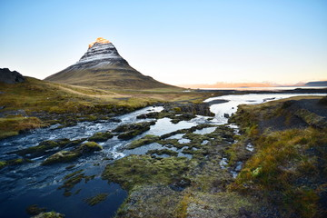 The scenic view of beautiful famous snowcapped mountain (Kirkjufell) with the foreground of flowing water of waterfall and river in near sunset time at Iceland.