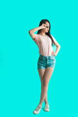 full size portrait of young slim asian student girl standing woth crossed legs isolated against studio blue wall