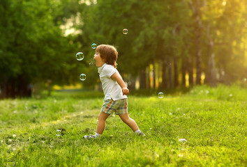 A 2 year old boy plays outside in the summer for soap bubbles.