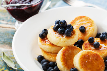Delicious cottage cheese pancakes or curd fritters decorated honey and blueberry. Healthy and diet breakfast.