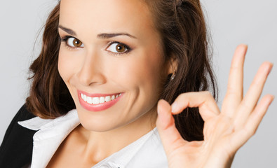 Happy business woman with okay gesture, over gray
